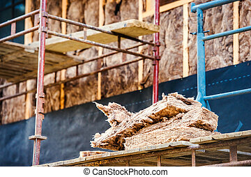 Pieces of glass insulation wool on scaffold against house -...