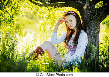 Young beautiful girl sitting on the grass and smiling, sunny...