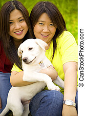 Best Friend - two beautiful asian women holding a labrador...