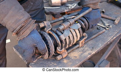 Auto mechanic working on shock absorber in garage - Auto...