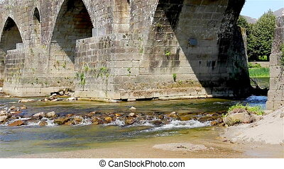 Medieval bridge with water flowing - The medieval bridge...
