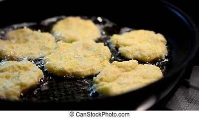 Frying potato pancakes - The cook moving potato pancakes in...
