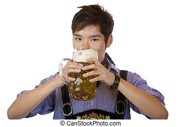 Asian man holding an Oktoberfest beer stein and drinks out...