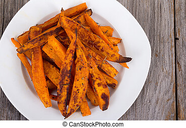 Sweet potato fries wedges closeup on wooden table
