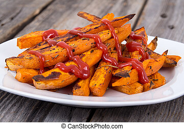 Sweet potato fries wedges closeup on wooden table with...