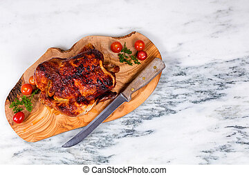 Large whole chicken ready to be served on wooden board -...