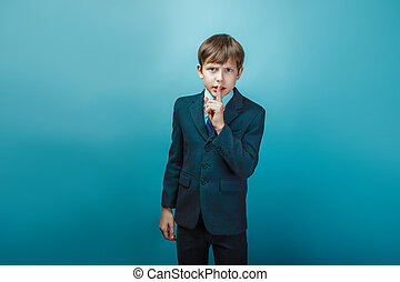 Boy in a suit with his finger on his mouth