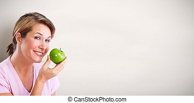 Mature smiling woman with apple. - Senior smiling woman with...