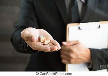 Businessman holding two dices and document
