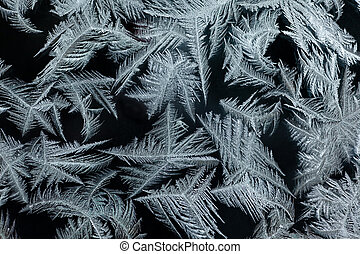 ice-flowers frost pattern tracery on frosted window -...