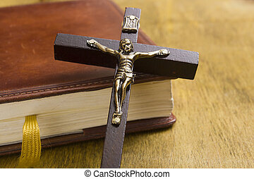 Catholic cross on the book - Catholic wooden cross with a...