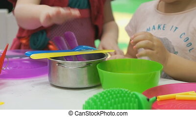 Two kids plays with plastic children's tableware - Two 5...
