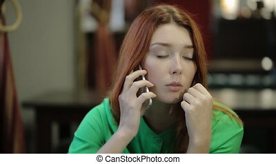 Young red-haired woman takes in hand the smartphone and listen thoughtfully, she looks to the side and down .