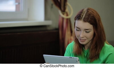 Beautiful, young, red-haired woman holding a tablet...