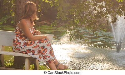 Blond Girl Sits on Bench at Fountain Plays with Iphone
