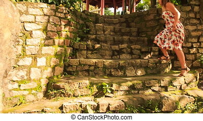 Blond Girl Goes up Stone Steps to Pavilion in Park - blond...