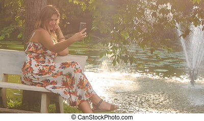 Blond Girl Sits on Bench at Fountain Waves Hand in Park -...