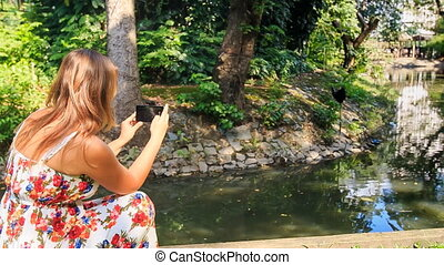 Closeup Backside Blond Girl Takes Photo of Stream in Park -...