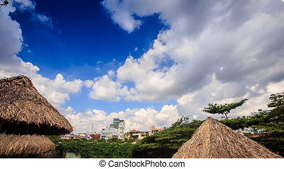 Clouds Motion in Sky above City Park Reed Sun Umbrellas -...