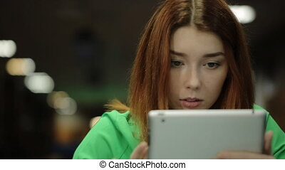 A young woman holds a finger on the touch screen tablet PC, stares at the screen and looks up