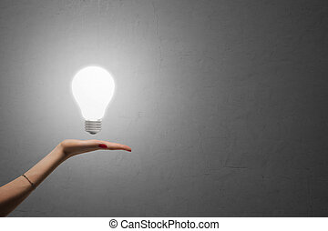 Glowing light bulb on palm, concrete wall in the background. Idea concept