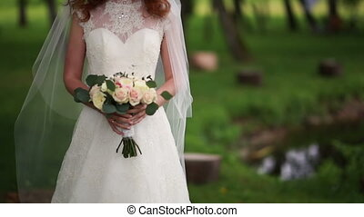 bride in a garden while holding a bouquet in hands