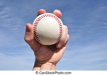 Player Gripping a New Baseball Against a Blue Sky