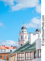 rooftops and church steeple against a blue sky