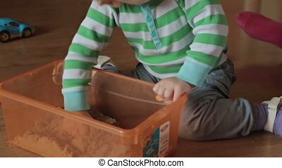 A cute little blond boy play with kinetic sand at home