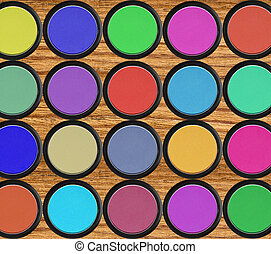 colorful eyeshadows in black boxes over wooden table