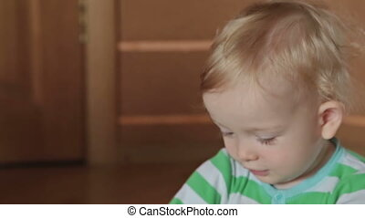 A cute little blond boy play with kinetic sand