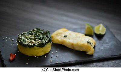 cod steak with potatoes on a basalt - juicy cod steak with...