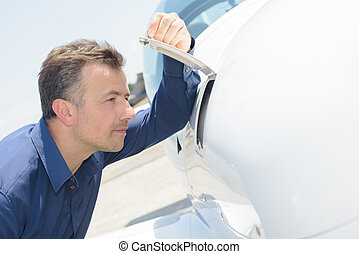 Man peering into compartment of airoplane