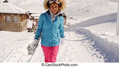 Smiling pretty young woman carrying a snowboard - Smiling...