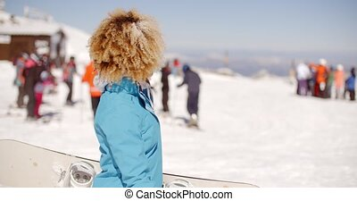 Trendy young woman carrying her snowboard - Trendy young...