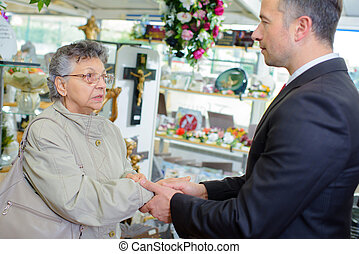 Undertaker shaking hand of elderly lady
