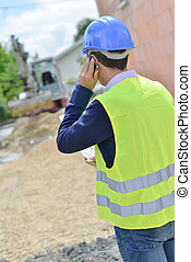 Man on telephone, looking at building site