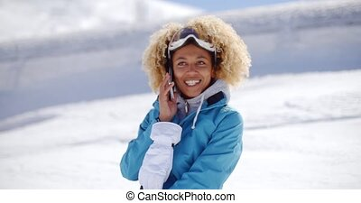 Happy adult in snowsuit with cell phone - Single woman in...