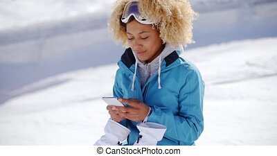 Woman in snowsuit checking phone - Single woman in blue...