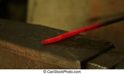 Farrier hammers on the red-hot piece of iron.