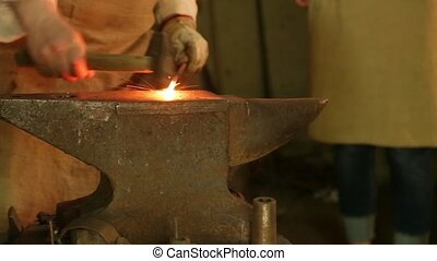 Blacksmith hammers on the red-hot piece of iron