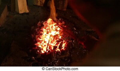 Smith stir the coals in the fire