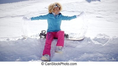 Beautiful young snowboarder sitting on snow
