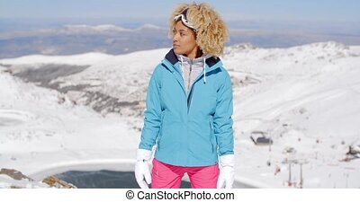 Beautiful woman in ski outfit standing on mountain - Single...