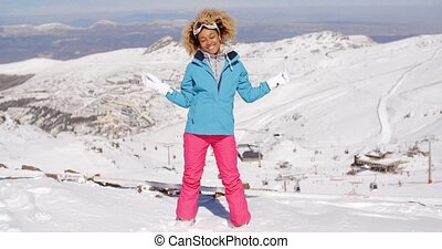 Single woman in ski clothes waving arms - Single beautiful...
