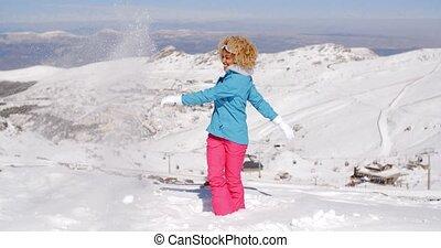 Cute woman in skiing clothes kicking snow - Single cute...