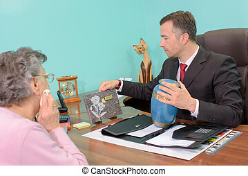 Undertaker with woman, holding plaque and urn