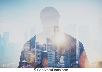 Photo of young man looking on the city, sunrise. Double...