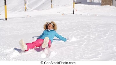 Young woman making a snow angel in white snow - Young woman...