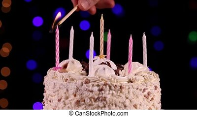 One's hand lit a candles of the birthday cake in front of...